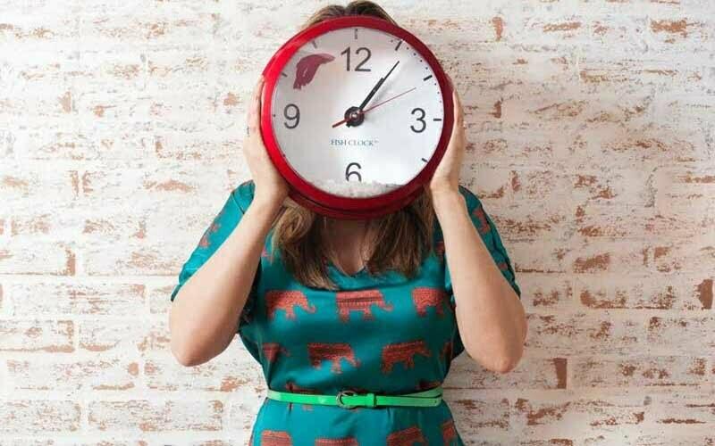 Frau hält große Uhr vor Gesicht