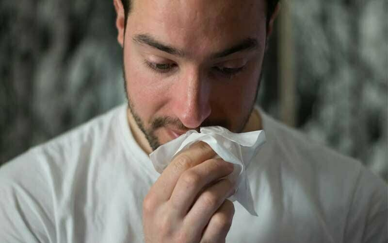 Mann benutzt Taschentuch