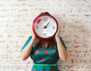 Frau hält große Uhr